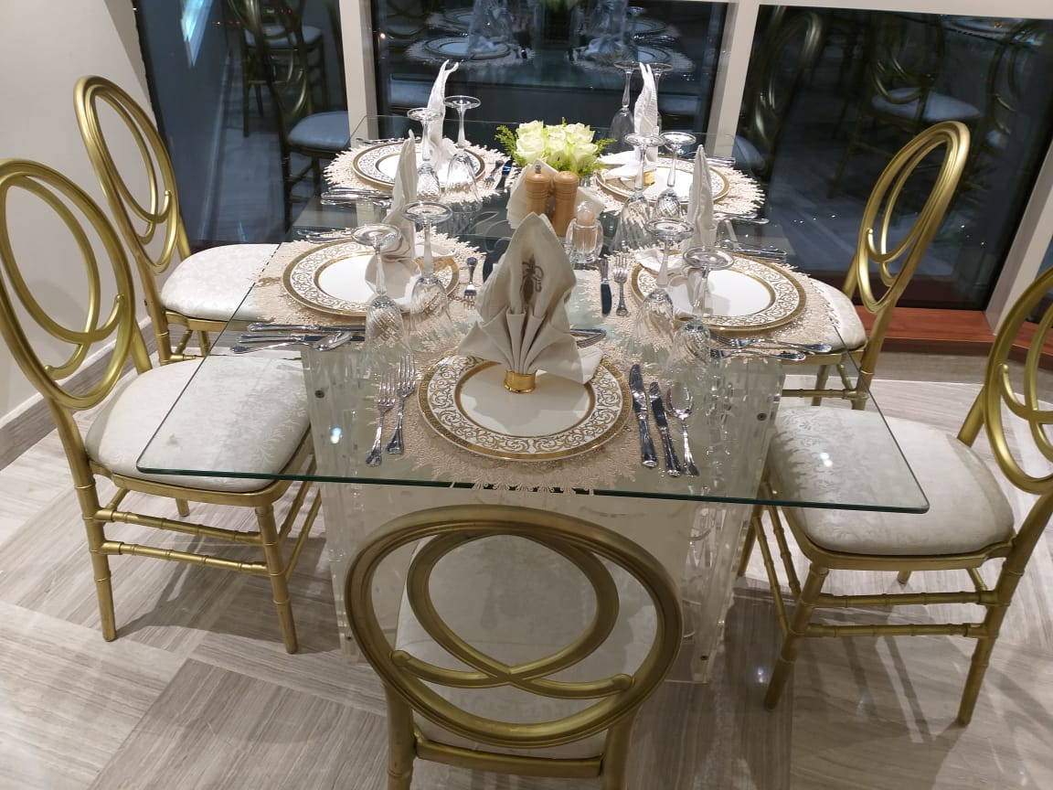 rectangular glass top table with gold acrilic chairs